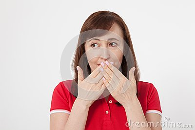 Beautiful woman covers her mouth with her hands for silent isolated. Red tshirt and keeping a secret.