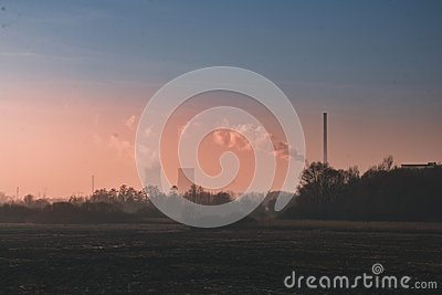 stock image of landscape with field and trees, in the distance factory and a po