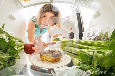 Diet struggle: A hand grabbing a donut from the open refrigerator full of greens.
