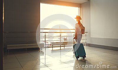 young woman waiting for flying at airport at window with suitcase