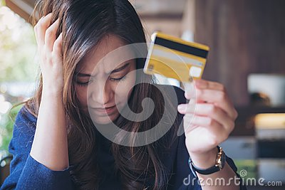 Woman close her eyes while holding credit card with feeling stressed and broke