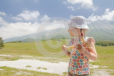 Travel holidays of little blonde girl in summer mountain valley