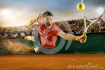 The one jumping player, caucasian fit man, playing tennis on the earthen court with spectators