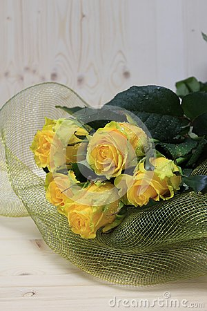 Buket of yellow roses, on a wooden table.