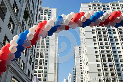 String of colorful balloons against apartment buildings and blue sky on background. Concept of outdoor celebration activities or e