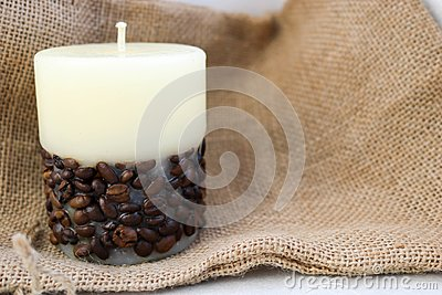 Wax beautiful light beige candle with unflavored wick from below decorated with coffee beans on the background of old brown canvas