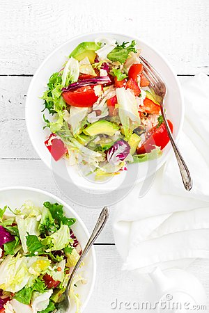 Healthy vegetable salad with fresh greens, lettuce, avocado, tomato, seet pepper and goat cheese. Delicious and nutritious diet d