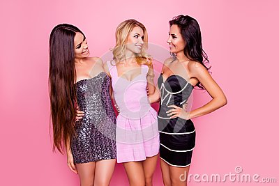 Portrait of three cute, nice, slim, attractive girls, in short dresses, looking to each other, having fun on new year party, stand