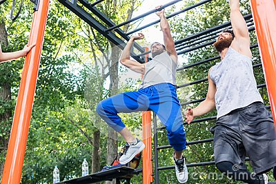 Two strong and competitive men exercising on monkey bars
