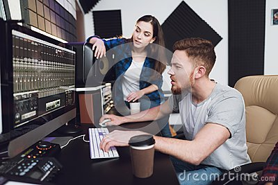 Two singers and sound engineers in the recording studio.