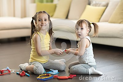 Conflict between little sisters. Kids are fighting, toddler girl takes toy, sibling relationships