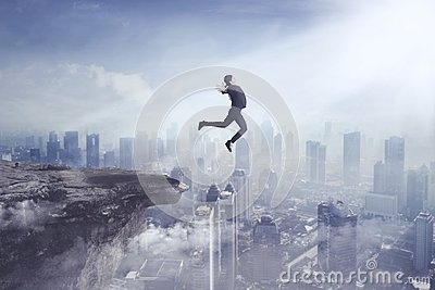 Young businesswoman jumping off a cliff