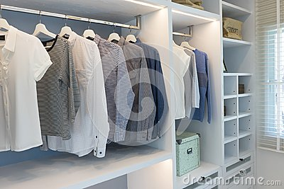 Cloths hanging in wooden wardrobe at home