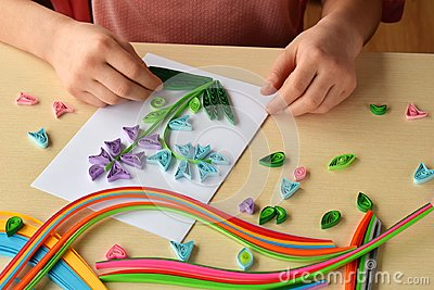 Quilling technique. Girl making decorations or greeting card. Paper strips, flower, scissors. Handmade crafts on holiday: Birthday