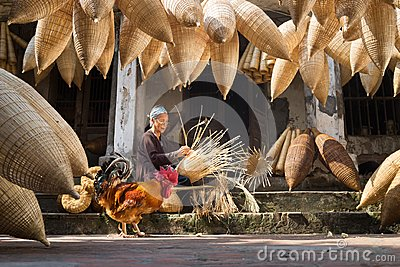 Hung Yen, Vietnam - July 9, 2016: Old house yard with many bamboo fish trap, a cock, and female craftsman making traditional bambo