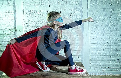 Female child 7 or 8 years old young girl performing happy and excited posing wearing cap and mask in super hero fantasy costume lo
