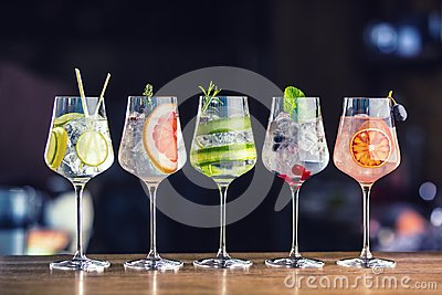 Five colorful gin tonic cocktails in wine glasses on bar counter