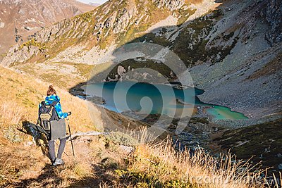 Woman hiker in the mountains and lake at background. Tourist woman descend from the mountain