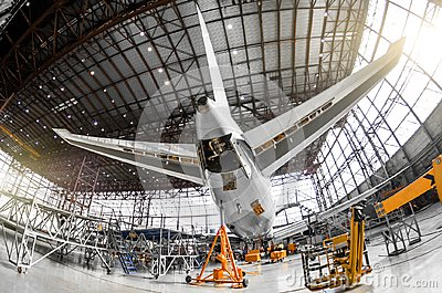Large passenger aircraft on service in an aviation hangar rear view of the tail, on the auxiliary power unitand tail altitude cont