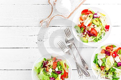 Healthy vegetable salad with fresh greens, lettuce, avocado, tomato, seet pepper and goat cheese. Delicious and nutritious diet di