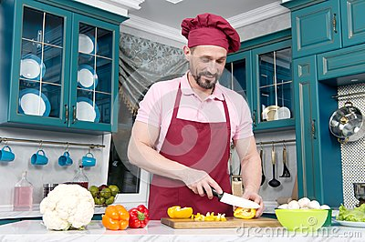 Guy with knife cutting orange pepper on table. Cook dressed in apron prepare dinner with paprika. Man in hat preparing vegetables.