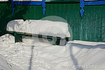 Green bench against a wall in white snow
