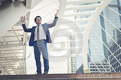 Asian businessman stand and raising up two hands to cheerful and celebrated his successful in career and mission.