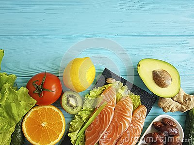 stock image of red fish omega 3 , fresh avocado nuts assortment on blue wooden, composition healthy food