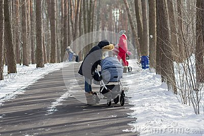 Mothers with strollers on a walk in the park in the winter