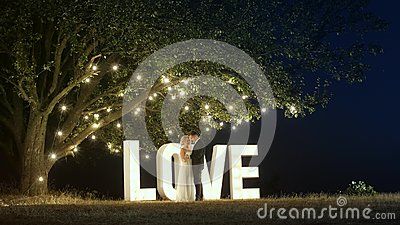 Young couple in love in evening dresses are dancing near love light letters.