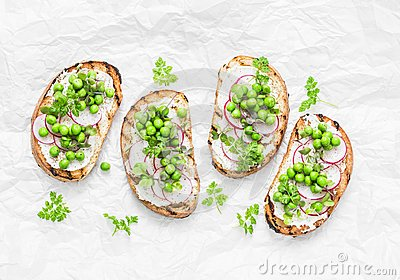 Grilled bread, soft cheese, green peas, radishes and micro greens spring sandwiches. Healthy eating, slimming, diet lifestyle conc
