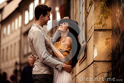 Passionate gorgeous young couple embrace each other while walk across ancient city. Cheerful elegant cute female model