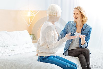 Expressive young woman telling an amazing story to her curious aged grandmother