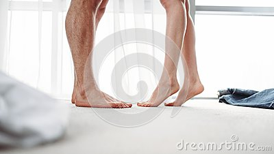 Male and female legs, intimate games in bedroom