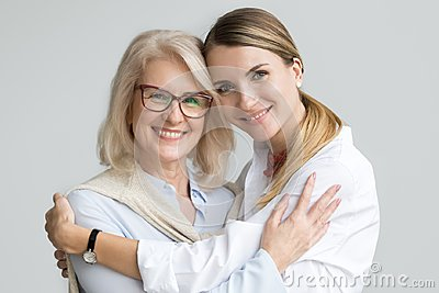 Happy older mother and adult daughter embracing looking at camer