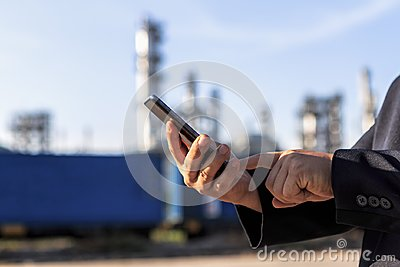 stock image of businessman checking around oil refinery plant with clear sky