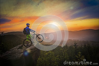 Mountain biker riding at sunset on bike in summer mountains fore