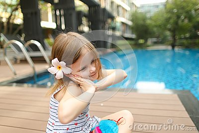 Cute small human girl kid sitting close to swimming pool wearing