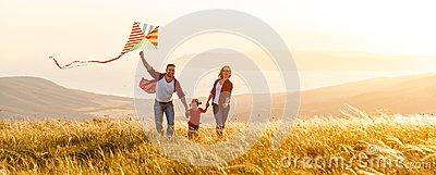 Happy family father, mother and child daughter launch a kite on