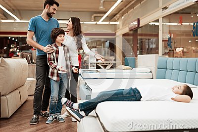 Blissful family buys new orthopedic mattress in furniture store. Happy family choosing mattresses in store.
