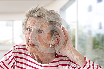 stock image of elderly lady with hearing problems due to ageing holding her hand to her ear as she struggles to hear, profile view on