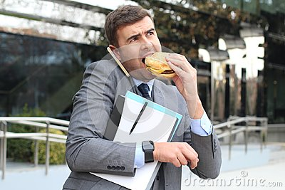 Overworked businessman eating fast food on the go
