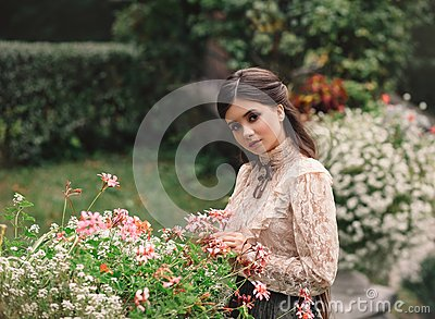 A girl walks in a flowering garden, she has a vintage blouse with a bow, chestnut long hair. she gently cares for her