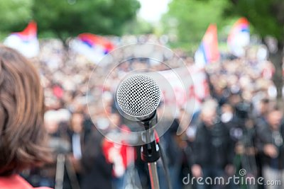 Political protest. Demonstration. Microphone in focus against bl
