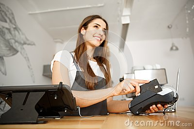 Coffee business concept - beautiful female barista giving payment service for customer with credit card and smiling