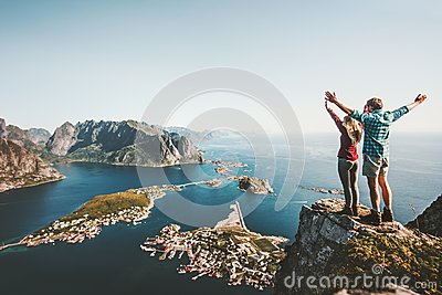 stock image of happy couple love and travel raised hands on cliff