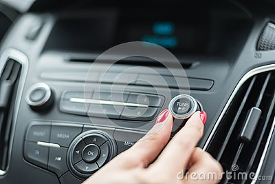 Woman changing frequency on car radio