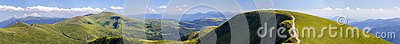 Panorama of green hills in summer mountains with gravel road for