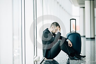 Business man sitting at the terminal airport on the floor with suitcase flight delay, two hands touch at head, headache, waiting t