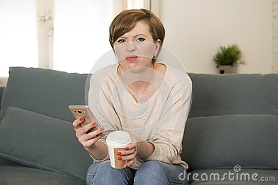 Young attractive 30s red hair woman upset bored and moody using internet app on mobile phone sitting at home sofa couch in annoyed